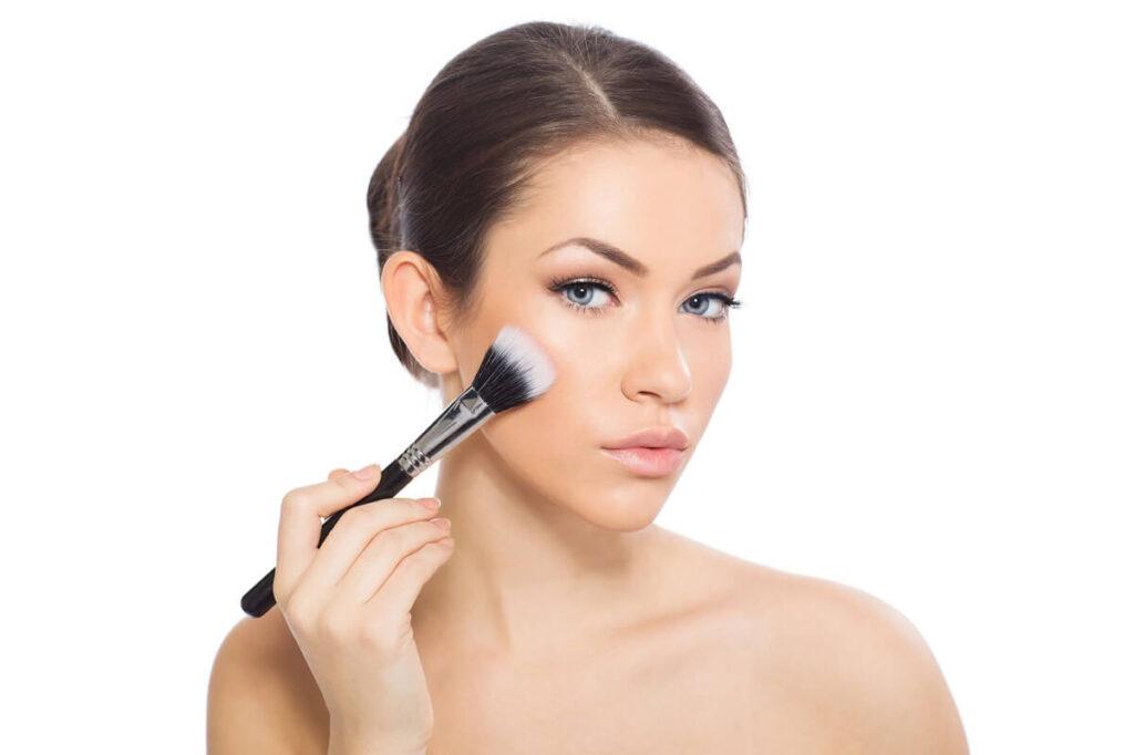 Žena nanáší make-up na obličej